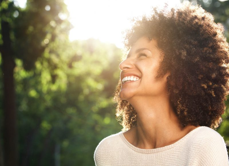 Close up portrait of beautiful confident woman laughing in nature