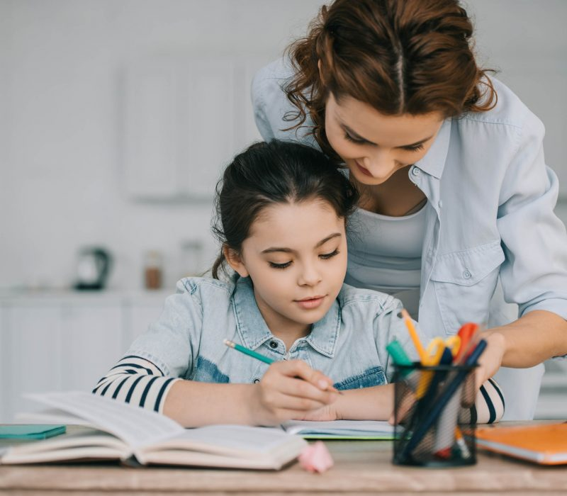 mom helping her child with best-guess spelling and homework at home